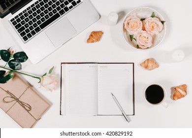 Workspace with diary, pen, vintage tray, pink rose, croissants and coffee on white background. Top view, flat lay