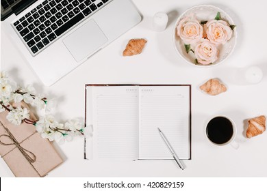 Workspace with diary, pen, vintage white tray, sakura, roses, croissants and coffee on white background. Top view, flat lay