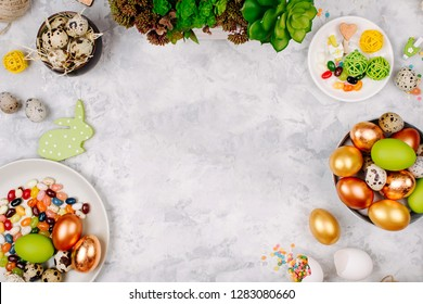 Workspace with easter decoration. Painted eggs in trays, candy, flowers with copy space. Holiday background. Flat lay, top view