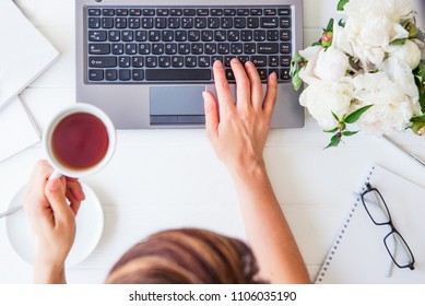 Workspace with girl's hand on laptop keyboard and cup of tea, notebooks, glasses, white peony flowers on white woodden background. Top view feminine office table desk. Freelancer working place.