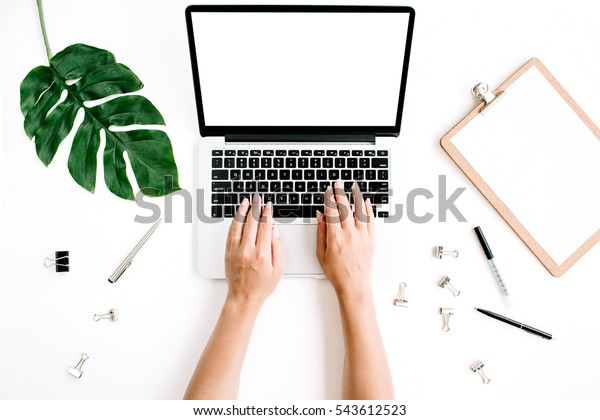Workspace with hands typing on laptop with blank screen. Flat lay, top view. Woman entrepreneur hero background with laptop