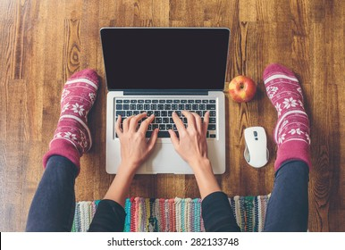 Workspace in home: fingers on laptop keyboard, red apple, legs in socks on a wooden floor and colored carpet