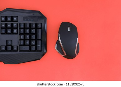 Workspace with a keyboard and mouse on a red background. Copyspace. Black mouse, keyboard isolated on a red background, top view. Flat lay gamer background. Copyspace
