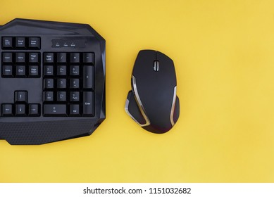Workspace with a keyboard and mouse on a yellow background. Copyspace. Black mouse, keyboard isolated on a yellow background, top view. Flat lay gamer background. Copyspace