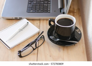 Workspace with a laptop, coffee, notebook, and a glasses