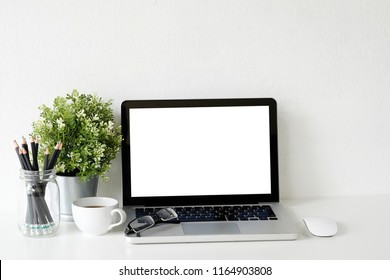 Workspace laptop computer, coffee cup and plant decorate on white office desk.