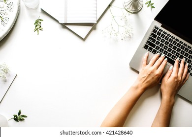 Workspace with laptop, girl's hands, notebook, sketchbook, white vintage tray, candlesticks on white background. Flat lay, top view office table desk. Freelancer working place - Shutterstock ID 421428640