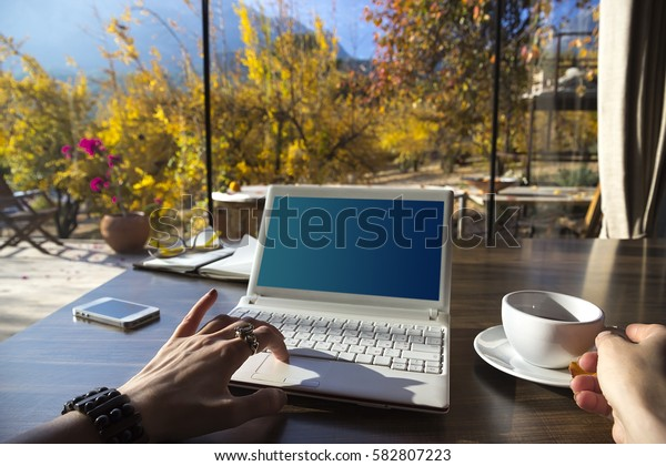 Workspace with laptop, girl's hands, notebook, sketchbook, glasses, on a  wooden desk In the background, Glass walls and a beautiful Yellow fruit garden early in the morning. Freelancer working place.