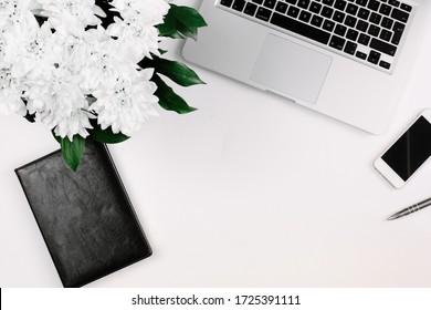 Workspace mit Laptop, Notebook, Smartphone, Stift und Blumenstrauß auf weißem Tisch. Flachlage, obere Ansicht