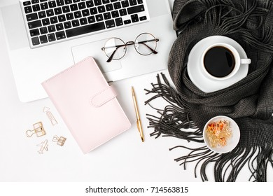 Workspace with laptop, planner, coffee cup wrapped in scarf, golden clips, glasses. Stylish office desk. Autumn or Winter concept.  Flat lay, top view
