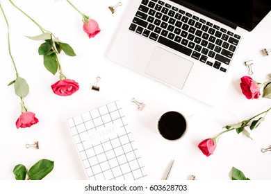 Workspace with laptop, red roses flowers, coffee cup, notebook and clips on white background. Flat lay, top view. Feminine background.