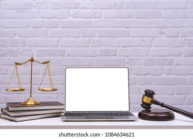 Workspace for lawyer with laptop blank screen and wooden gavel , legal law on wood table in office. Workspace background and desk work mockup concept.