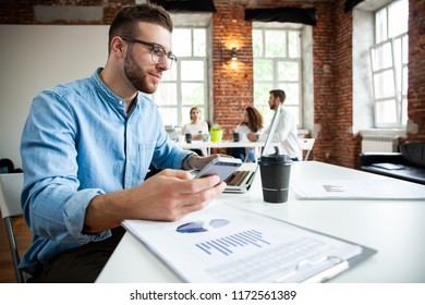 Workspace lifestyle concept. Businessman using smartphone. Handsome businessman is using a smartphone and smiling while working in office