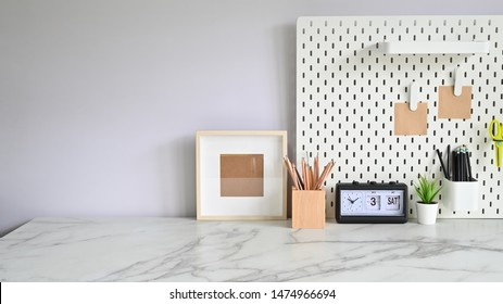 Workspace Mock up marble table with pencils, photo frame with pegboard and houseplant.