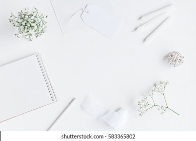 Workspace with notebook, paper blank, gypsophila flowers, pencils. Wedding concept. Flat lay, top view.