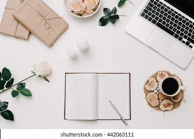 Workspace with opended diary, laptop, rose, coffee on white background