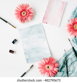 Workspace. Pink gerbera buds and watercolor paper with paintbrush and blue textile on white background. Flat lay, top view