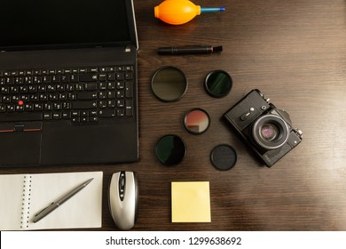 Workspace of professional photographer. Photography and office equipment on the dark desktop.