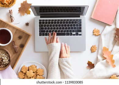 Workspace with red and yellow maple leaves, laptop, cup of tea, sweet homemade cookies. Top view of cozy office desk. Autumn background, flat lay.