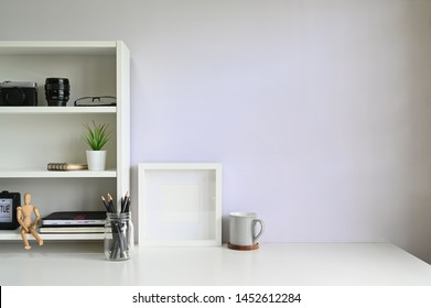 Workspace shelves with camera, lens with photo frame and coffee mug on table.