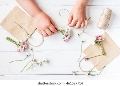 Workspace with small bouquets of daisy flowers, paper bags. Kid's hands making flower composition. Top view, flat lay
