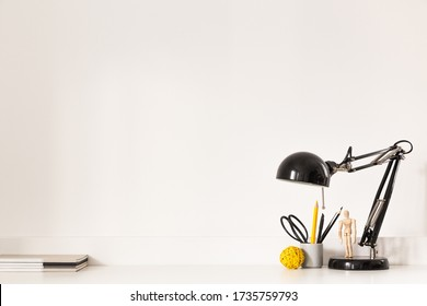 Workspace, stylish lamp, school supplies - desk near white wall. Stylish and minimal home office workplace.