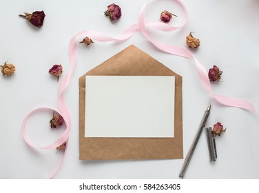 Workspace. Wedding invitation cards, craft envelopes, pink and red roses and green leaves on white background. Overhead view. Flat lay, top view wedding invitation card Templates