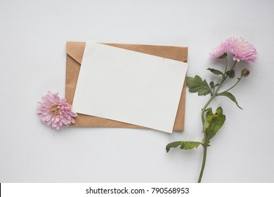 Workspace. Wedding invitation cards, craft envelopes, pink flowers and green leaves on white background. Overhead view. Flat lay, top view invitation card. ink pen, ink with copy space. mockup