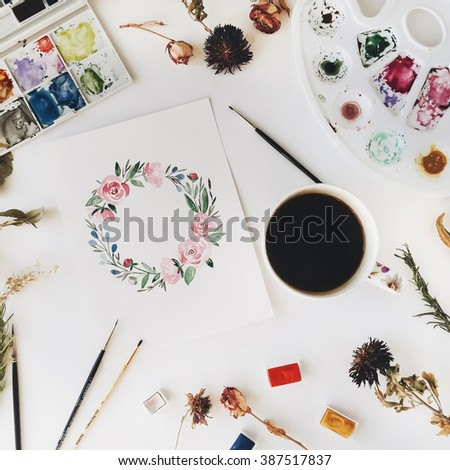 Workspace. Wreath with flowers and leaves painted with watercolor, paintbrush and cup of black coffee isolated on white background. Overhead view. Flat lay, top view