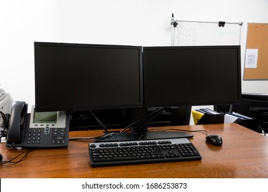 Workstation in modern office interior with dual black monitors on wooden desk close up