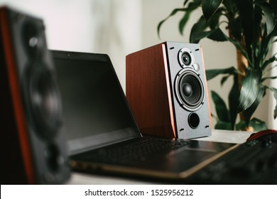 Workstation with speakers and computer in studio. Desktop in home office. Selective focus on the speaker.