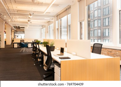 Workstations sprawl across a modern,  open concept office building. Natural light fills the room from large windows along the walls.