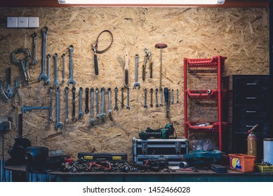 Worktop with vise and workshop tools on the background of hanging spanners.