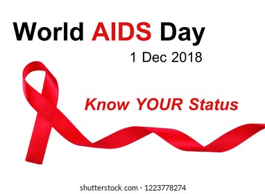 "World AIDS Day concept, red ribbon on white background with text ""World AIDS Day 2018, Know Your Status"", an international day dedicated to raising awareness of the AIDS with this year's theme"