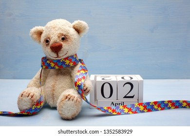 World Autism Awareness day, concept with teddy bear holding puzzle or jigsaw pattern on heart and calendar