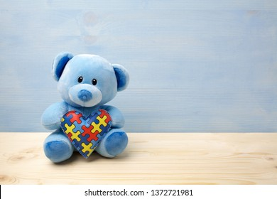 World Autism Awareness day, concept with teddy bear holding puzzle or jigsaw pattern on heart