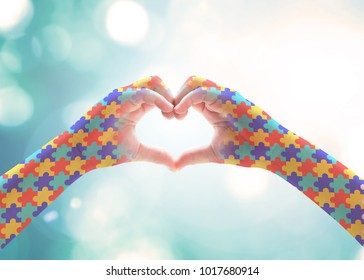 World Autism Awareness day, mental health care concept with puzzle jigsaw pattern on heart shape kid's hands for supporting autistic child medical charity campaign