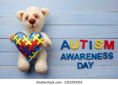 World Autism Awareness day, mental health care concept with teddy bear holding puzzle or jigsaw pattern on heart
