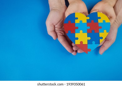 World Autism Awareness day, mental health care concept with puzzle or jigsaw pattern on heart with child and adult hands