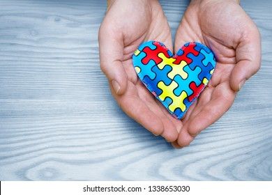 World Autism Awareness day, puzzle or jigsaw pattern on heart with father hands