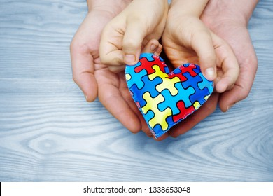 World Autism Awareness day, puzzle or jigsaw pattern on heart with autistic child's and father hands