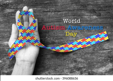 World Autism awareness day with Puzzle ribbon on person's hand