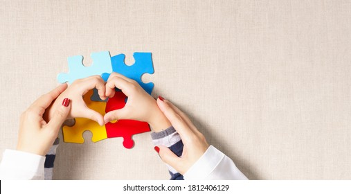 World autism awareness day, understanding  love concept, a beautiful mother holding hands of little autistic child making heart shape over symbol colored puzzle. ASD, April 2, Top view banner.