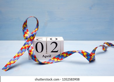 World Autism awareness and pride day with Puzzle pattern ribbon and calendar on blue wooden background