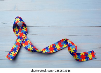 World Autism awareness and pride day or month with Puzzle pattern ribbon on blue wooden background.