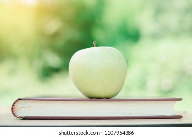 World Book Day concept. Green apple and stack of old books