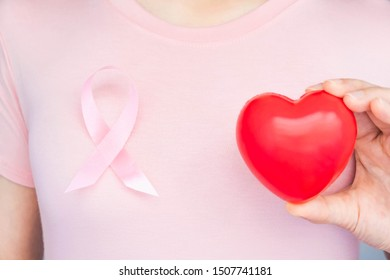 World Breast Cancer Day,health care, woman wore pink t-shirt,hold Red heart and Pink ribbon for breast cancer awareness, symbolic bow color raising  on people living,women's breast tumor illness