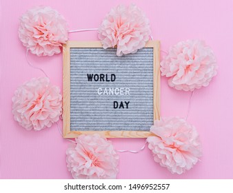 World Cancer Day is 4th February. Breast Cancer Awareness Month October. Mood felt letter board wit text and pink flowers flat lay