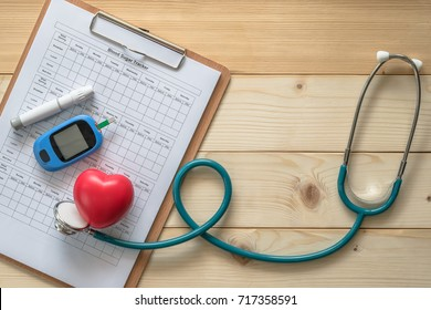 World diabetes day, National American diabetic awareness month concept with blood drop examination tool kit, blood sugar tracker record and heart with doctor's stethoscope