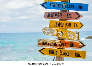 World direction signpost with distance to many different countries in the beach.